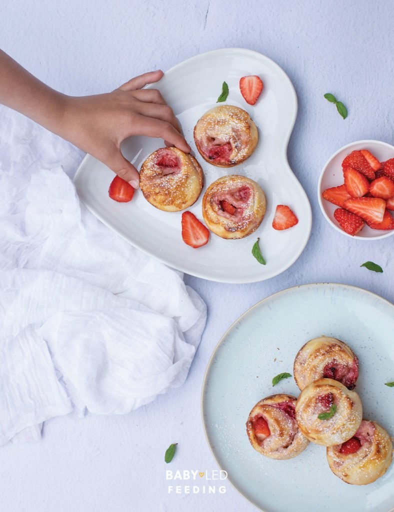 Strawberry and Cream Cheese Pinwheels with hand taking.